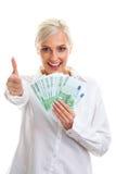 Mujer joven feliz que lleva a cabo cuentas euro imagen de archivo