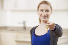 Mujer joven feliz que lleva a cabo llaves al nuevo hogar Fotos de archivo
