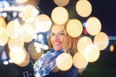 Mujer joven feliz que lleva a cabo luces de hadas en la noche fría en ciudad imagen de archivo libre de regalías
