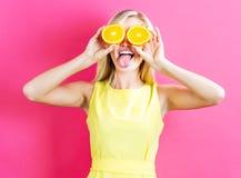 Mujer joven feliz que lleva a cabo mitades de las naranjas Foto de archivo
