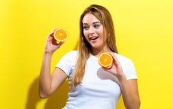 Mujer joven feliz que lleva a cabo mitades de las naranjas Imagen de archivo libre de regalías