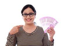 Mujer joven feliz que lleva a cabo 2000 notas de la rupia Imagen de archivo