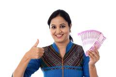 Mujer joven feliz que lleva a cabo 2000 notas de la rupia y que hace el pulgar para arriba Foto de archivo