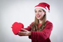 Mujer joven feliz que lleva a cabo un corazón grande presente para el día de Cristmas Foto de archivo libre de regalías
