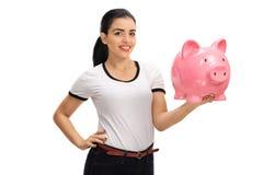 Mujer joven feliz que lleva a cabo un piggybank Imágenes de archivo libres de regalías