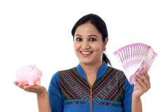 Mujer joven feliz que lleva a cabo una hucha y notas de la rupia india Foto de archivo libre de regalías