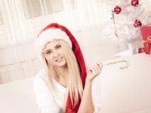 Mujer joven feliz que lleva el sombrero de Santa Claus Foto de archivo libre de regalías
