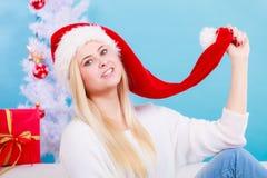 Mujer joven feliz que lleva el sombrero de Santa Claus Imagenes de archivo