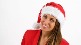 Mujer joven feliz que lleva un sombrero de Papá Noel Foto de archivo libre de regalías