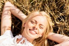 Mujer joven feliz que miente en campo de cereal Foto de archivo