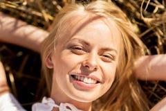 Mujer joven feliz que miente en campo de cereal Imagen de archivo