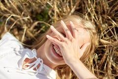 Mujer joven feliz que miente en campo de cereal Fotografía de archivo