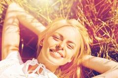 Mujer joven feliz que miente en campo de cereal Fotos de archivo