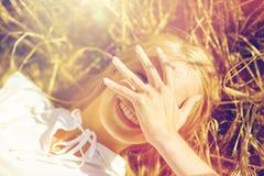 Mujer joven feliz que miente en campo de cereal Foto de archivo libre de regalías