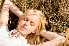 Mujer joven feliz que miente en campo o el heno de cereal Fotos de archivo