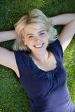 Mujer joven feliz que miente en hierba Fotografía de archivo libre de regalías