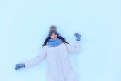 Mujer joven feliz que miente en nieve en invierno Imagen de archivo libre de regalías
