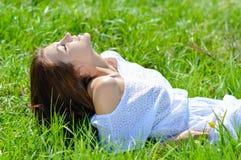 Mujer joven feliz que miente en vestido blanco corto del verano en hierba verde Foto de archivo