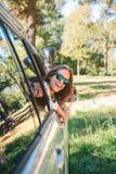 Mujer joven feliz que mira detrás a través del coche de la ventana Imagen de archivo