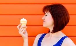 Mujer joven feliz que mira el helado con una sonrisa delante de la pared anaranjada Colores y concepto brillantes de la felicidad foto de archivo libre de regalías