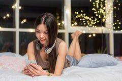 Mujer joven feliz que mira el móvil Foto de archivo