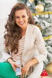 Mujer joven feliz que mira el árbol de navidad cercano remoto de la TV Imagen de archivo libre de regalías