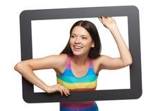 Mujer joven feliz que mira furtivamente fuera de marco de la tableta Imagen de archivo libre de regalías