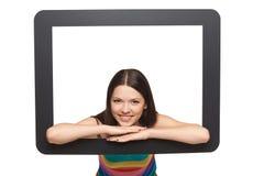 Mujer joven feliz que mira furtivamente fuera de marco de la tableta Fotos de archivo libres de regalías