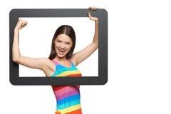 Mujer joven feliz que mira furtivamente fuera de marco de la tableta Imagenes de archivo
