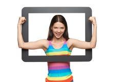 Mujer joven feliz que mira furtivamente fuera de marco de la tableta Fotografía de archivo