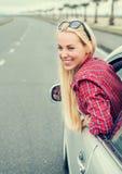 Mujer joven feliz que mira hacia fuera de la ventanilla del coche fotos de archivo