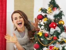 Mujer joven feliz que mira hacia fuera del árbol de navidad Fotos de archivo libres de regalías
