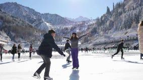 Mujer joven feliz que mira la cámara, muchachas del patinaje de hielo en la pista almacen de video