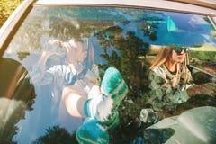 Mujer joven feliz que mira un mapa dentro del coche Imagen de archivo libre de regalías
