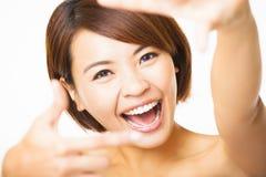 Mujer joven feliz que muestra el finger del marco Imagen de archivo libre de regalías
