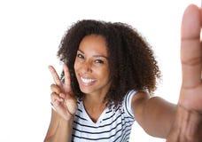 Mujer joven feliz que muestra el signo de la paz en selfie Imagen de archivo