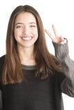 Mujer joven feliz que muestra gesto de la victoria Imagen de archivo libre de regalías
