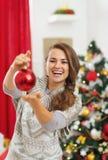 Mujer joven feliz que muestra la bola de la Navidad Foto de archivo libre de regalías
