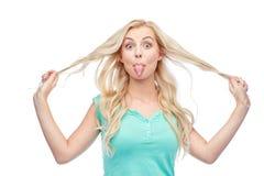 Mujer joven feliz que muestra la lengua y que sostiene el pelo Imágenes de archivo libres de regalías