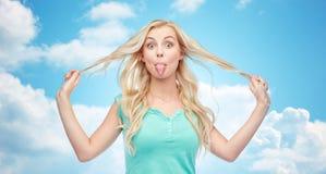 Mujer joven feliz que muestra la lengua y que sostiene el pelo Imagen de archivo libre de regalías