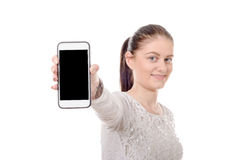 Mujer joven feliz que muestra la pantalla en blanco del smartphone Fotos de archivo libres de regalías