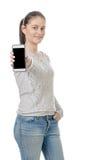 Mujer joven feliz que muestra la pantalla en blanco del smartphone Foto de archivo libre de regalías