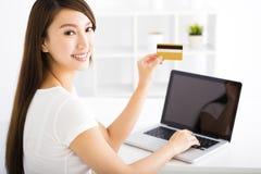 Mujer joven feliz que muestra la tarjeta de crédito y el ordenador portátil imagen de archivo libre de regalías