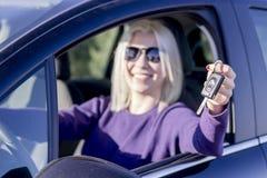 Mujer joven feliz que muestra llaves de su primera vista lateral automotriz imagenes de archivo