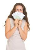 Mujer joven feliz que oculta detrás del ventilador de euros Foto de archivo