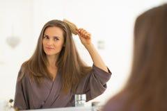 Mujer joven feliz que peina el pelo en cuarto de baño fotografía de archivo