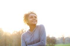 Mujer joven feliz que piensa y que mira para arriba Imagenes de archivo