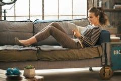 Mujer joven feliz que pone en el diván y que usa la tableta fotos de archivo libres de regalías