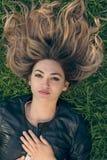 Mujer joven feliz que pone en la hierba en parque Foto de archivo libre de regalías