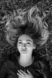 Mujer joven feliz que pone en la hierba en parque Fotografía de archivo